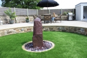 <h5>Plum slate Monolith</h5><p>A water feature sunk in the garden, in this beautiful landscape project</p>